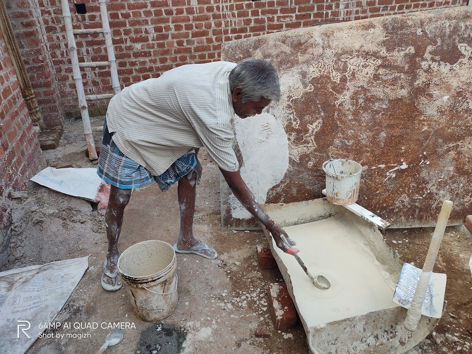 An old mason plasters the wall using lime in different layers