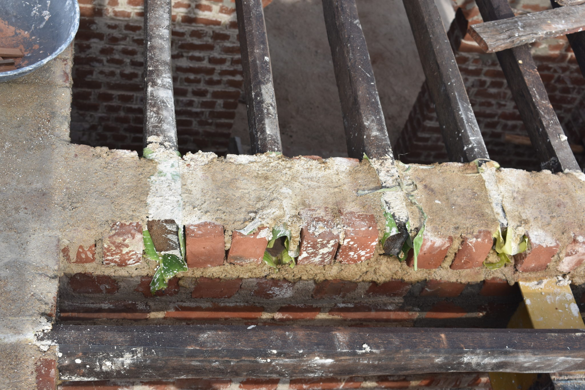 Plantain leaves being used between wood and the bricks to prevent termite attack.